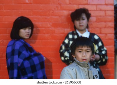 Three Chinese people standing against a red bricked building, San Francisco, CA