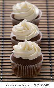 Three chocolate cupcakes with vanilla frosting in a row