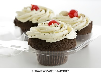 Three chocolate cupcakes with white frosting and red cherry