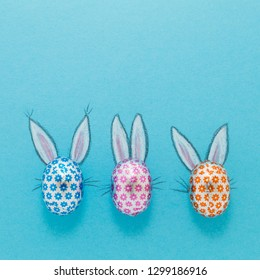 Three chocolate eggs in colorful aluminium foil with painted easter bunny ears on blue background