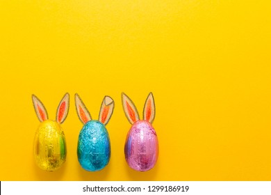 Three chocolate eggs in colorful aluminium foil with painted easter bunny ears on yellow background