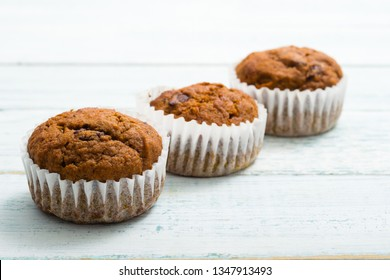 three chocolate muffins at paper cup, old white wooden table