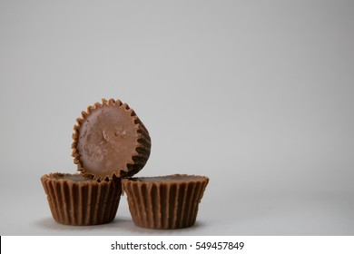 Three Chocolate Peanut-butter Cups Stacked on Top of Each Other Against a White Background
