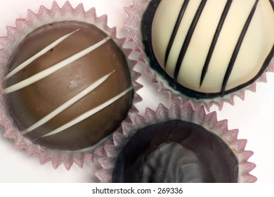 Three chocolate truffles of different types on a white background.