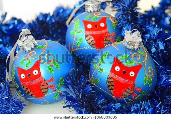 Three Christmas balls with owl on background of shiny blue tinsel