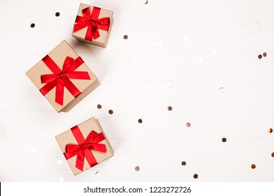 Three christmas craft gift boxes with glitter on white wooden background. Flat lay. Festive concept.