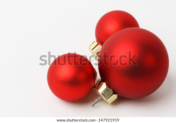 Three Christmas red balls on white background - horizontal
