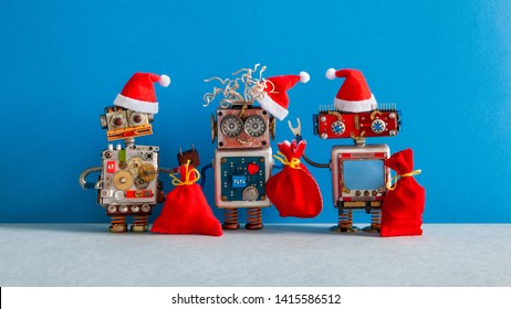 Three Christmas Santa Claus robotic toys dressed in red holiday hat. Funny smiley robots with a bags of gifts on blue background. For robot standing on the right copy space for text message or data