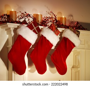 THREE CHRISTMAS STOCKINGS HANGING ON A FESTIVE MANTELPIECE