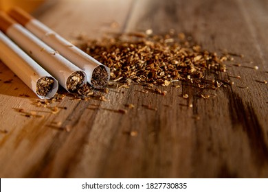 three cigarettes and some tobacco on a wooden board