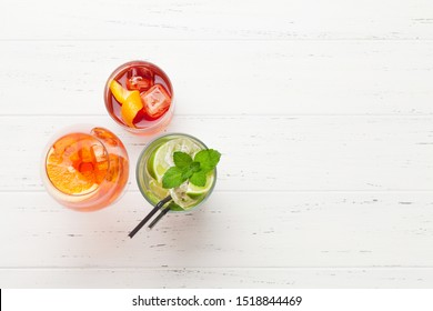 Three classic cocktail glasses on wooden table. Negroni, aperol spritz and mojito. Top view with copy space
