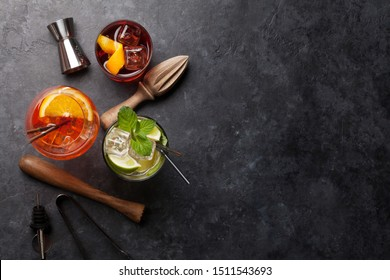 Three classic cocktail glasses and utensils on stone table. Negroni, aperol spritz and mojito. Top view with copy space. Flat lay