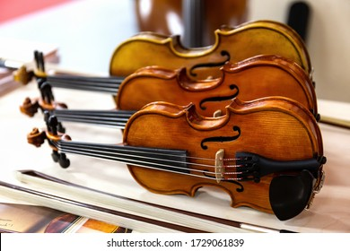 Three classical violins standing on a table. Stringed musical instruments of a Symphony orchestra.