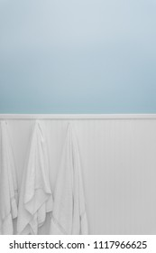 Three clean white towels hang from hooks on white beadboard or wainscoting with light blue wall paint