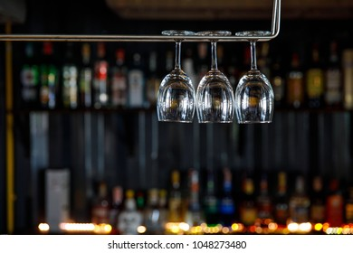 Three clear glasses hanging on shelf in restaurant with dark blur bottles in background