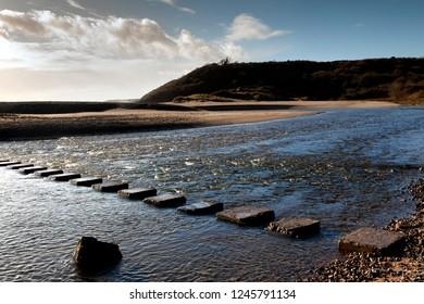 Three Cliffs Bay stepping stones The stepping stones that allow access over the river to the divided beaches at Three Cliffs Bay on the Gower peninsula in Swansea, South Wales, UK