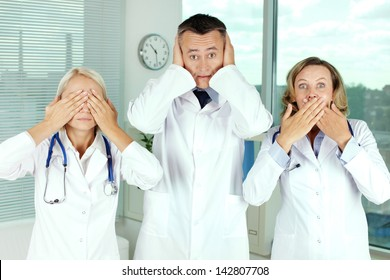 Three clinicians in white coats covering eyes, mouth and ears