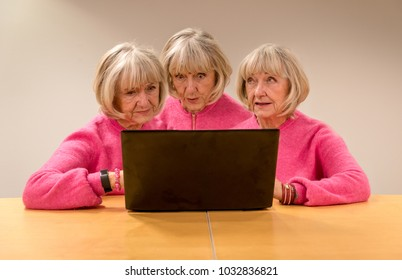 Three clones of one woman working and collaborating with a pc having different facial expressions