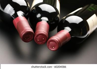 Three closed red wine bottles lying on dark background.