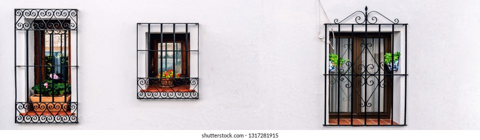Three closed windows with steel lattice on a whitewashed wall in a row outdoors view. Andalusian Mijas white village. Costa del Sol. Europe, southern Spain copyspace white background for your text