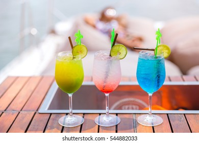 Three cocktail glasses in a row with different colors drinks