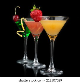 Three cocktails cosmopolitan cocktails decorated with citrus lemon twist yellow martini drink with strawberry isolated on a black background