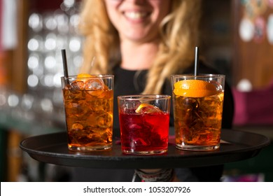 three cocktails on a tray, two spritz and one negroni, on the back ground a smiling blonde waitress