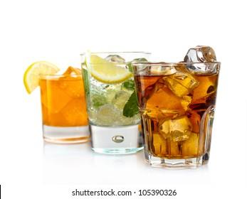 Three cocktails with orange juice, soda, lemon, mint and coke