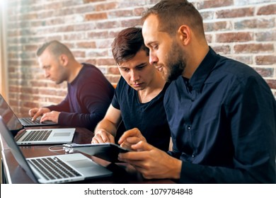 Three coders working on a project. Team of creative successful people solving a problem.