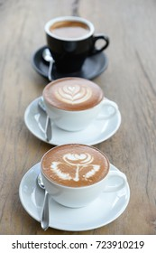 Three cofffee cup with latte art rose flower shape in the first cup another cup is hearth and leaf pattern,the last in black cup is black coffee