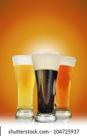 Three cold beer glasses have foam and are on a golden background with a highlight to add tour text message. Use it for a Bar or celebration concept.