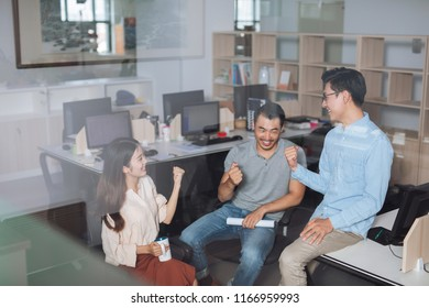 Three colleagues discussing and celebrating in the office.