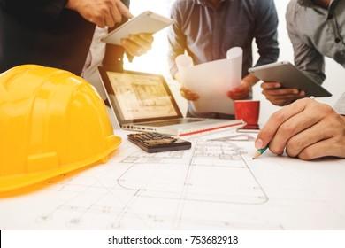 Drei Kollegen diskutieren über Datenverarbeitung und Tablet, Laptop mit über Architekturprojekt auf Baustelle am Schreibtisch im Büro