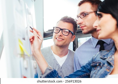 Three colleagues standing in front of a board and writing something on it