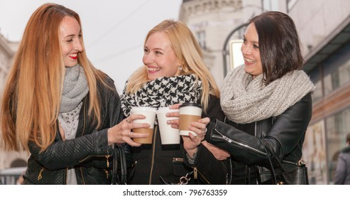 three colleges going out downtown having hot coffee drinks cheering each other. they wear leather jackets and scarfs. they are happy smiling and having fun. it is a big friendship which connects them