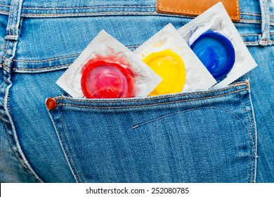 Three colored condoms in a jeans pocket.