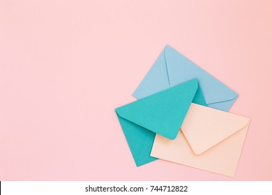 Three colored envelopes on pink background. Minimalist styled composition, top view, correspondence concept.