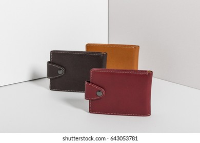 three colored leather wallet on the grey background.
