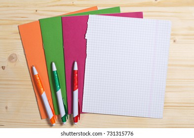Three colored pens, school notebooks and empty sheet on wooden desk, top view. Space for text