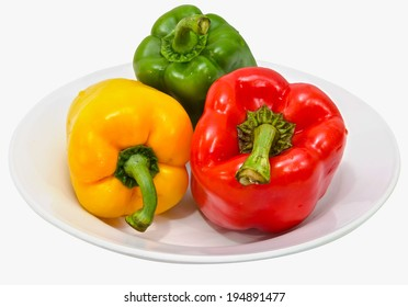 The three colored peppers on the plate isolated on white background.