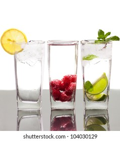 Three colorful alcoholic drinks with berries, fruit and ice. On a table with reflection and isolated over white.