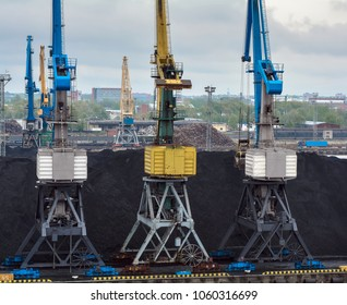 Three colorful blue and yellow cranes and a pile of coal on a harbor in Riga