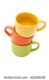 Three colorful ceramic cups, yellow,orange and green, stand on each other on a white background
