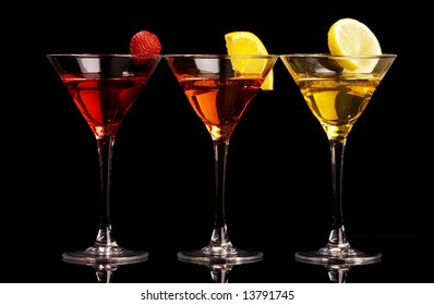 Three colorful cocktails with fruits on black background