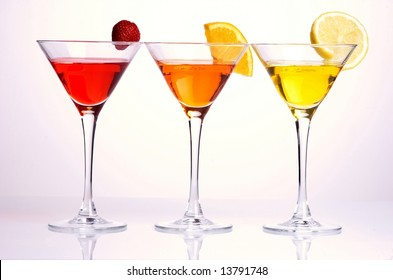 Three colorful cocktails with fruits on white background