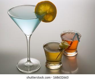 Three colorful cocktails glasses with citrus garnishment