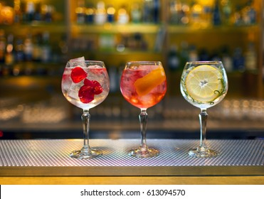 Three colorful cocktails in large wine glasses in a classic bar environment with dozens of blurry liquor bottles in the background.