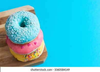 Three colorful frosting fried american donuts blue background