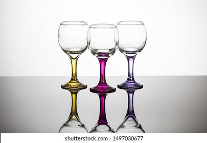 three colorful glass empty cups standing on a black and reflective plexiglass backdrop. there is a gradient light transition at the back