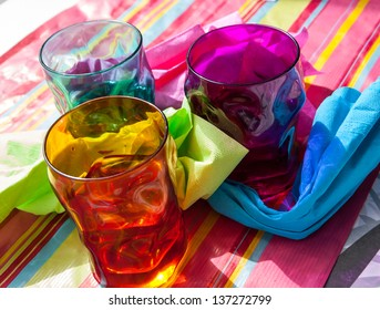 Three colorful glasses and napkins on multicolored paper tablecloth.
